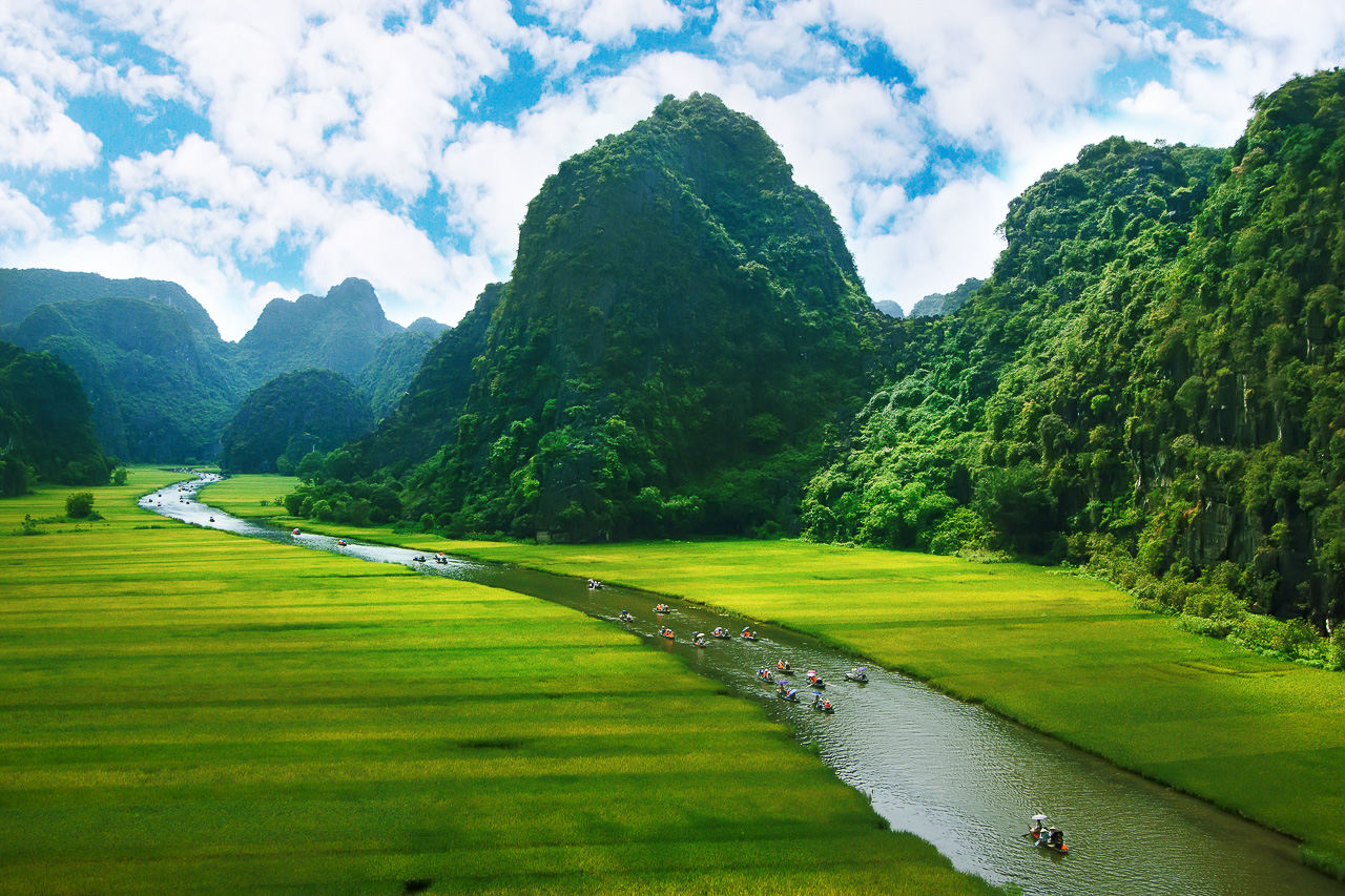 Take a river boat tour through rice fields between limestone peaks in Ninh Binh, Vietnam