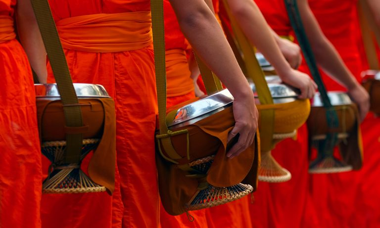 Buddhist monks with alms bowls collecting daily offerings in Luang Prabang, Laos
